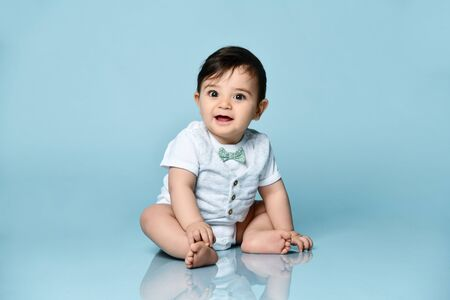 Baby boy in white bodysuit as a vest with bow-tie, barefoot. He is smiling, sitting on floor against blue studio background. Concept for articles about childhood or advertising for babies. Close up