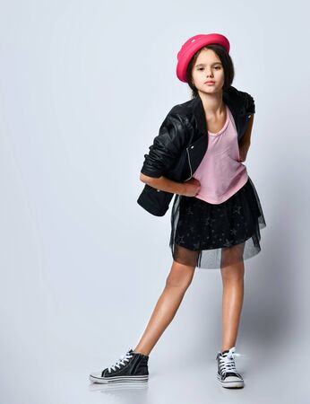 Teenage female in black leather jacket, skirt, t-shirt, pink hat and sneakers. She has folded her hands, posing standing isolated on white. Hipster style, fashion, beauty. Copy space. Full length 版權商用圖片