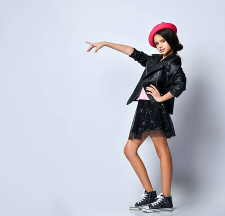 Brunette teenager in black leather jacket, skirt, t-shirt, pink hat and sneakers. She pointing at something, posing sideways isolated on white. Hipster style, fashion, beauty. Copy space. Full length