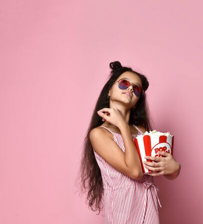 Brunette teenager with fancy hairstyle, in striped dress and aviator sunglasses. She smiling, holding pack of popcorn, posing on pink background. Fashion, beauty, cinema entertainment. Close up