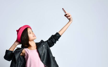 Brunette teenage kid in black leather jacket, skirt, t-shirt and pink hat. She taking selfie using her smartphone, posing isolated on white. Hipster style, fashion, beauty. Copy space. Close up