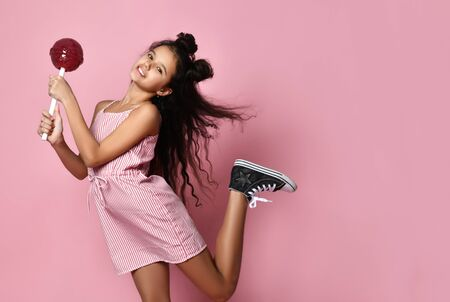 Brunette teenage child with fancy hairstyle, in striped dress and sneakers. She is smiling with raised leg, holding big red lollipop while posing on pink background. Fashion, beauty, sweets. Close up