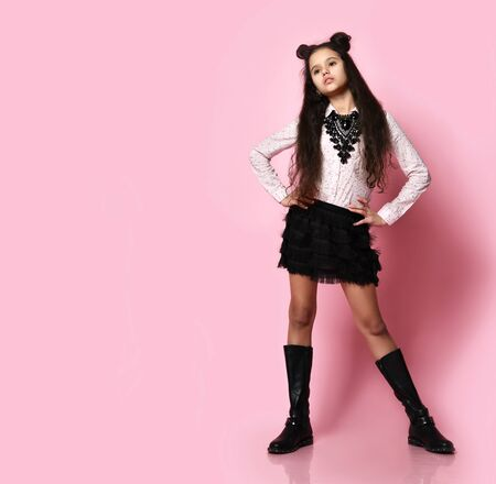 Young slim beautiful brunette curly girl model in stylish skirt, blouse, black boots and accessories posing over pink background in photo studio. Trendy youth casual fashion and beauty concept