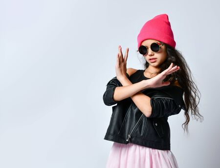 Teenage kid in black leather jacket, skirt, t-shirt, pink hat and sunglasses. She showing stop or no sign with gesture, posing isolated on white. Hipster style, fashion, beauty. Copy space. Close up 版權商用圖片