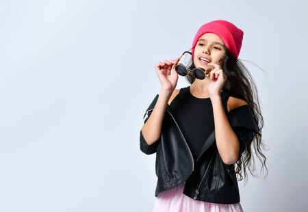 Brunette teenage child in black leather jacket, skirt and pink hat. She holding her sunglasses, posing standing isolated on white. Hipster style, fashion, beauty. Copy space. Close up 版權商用圖片