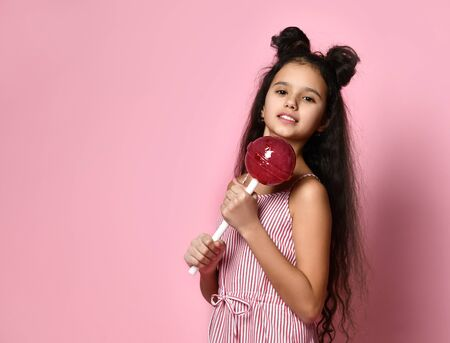 Brunette teenage kid with fancy hairstyle, in striped dress. She is looking wondered, holding a huge red lollipop while posing on pink studio background. Concept of fashion, beauty, sweets. Close up 版權商用圖片