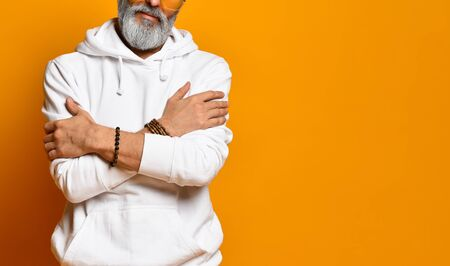Cropped photo of a male aging male with a beard in a white sweatshirt, pants and bracelets. He hugs himself, posing on an orange background. Fashion and Style. Close copy space Zdjęcie Seryjne - 140601006