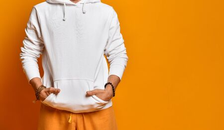 Cropped photo of man in a white sweatshirt, pants and bracelets. Folded hands in pockets and posing on an orange background. Fashion and Style. Close copy space