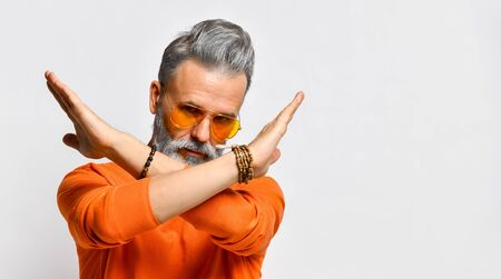 Gray-haired, bearded, aged male in orange sweater and sunglasses, bracelets. Showing stop sign by crossed hands while posing isolated on white background. Fashion and style. Close up, copy space