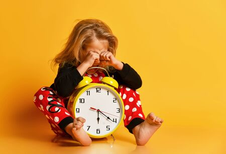 Little blond girl in red dotted pajamas sitting on floor with big alarm clock, feeling tired, yawning and rubbing eyes over yellow background. Different times of day and children schedule concept