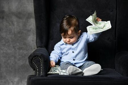 Little baby in blue shirt, gray pants, white booties. He holding some dollar notes, sitting in black armchair on gray background. Articles about childhood or advertisement for toddlers. Close up