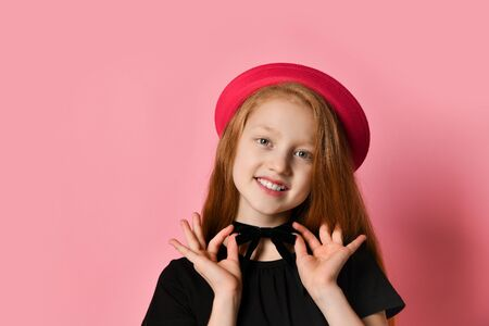 Red-headed teen female in black dress and red hat. She smiling, holding on to choker, posing against pink studio background. Hipster style, fashion, beauty. Close up, copy space