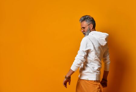 Photo cool looking mature white beard hipster guy, dancing weird youth moves a little drunk wearing sunglasses white hoodie and wide pants outfit, isolated yellow color background