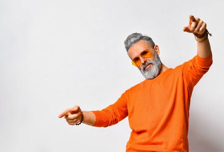 Gray-haired hipster man, bearded, in orange sweater and sunglasses, bracelets. Pointing at you by his forefingers while posing isolated on white background. Fashion and style. Close up, copy space