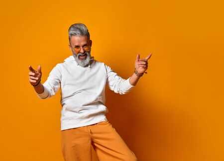 bearded, elderly male in years in white hoodie, pants and sunglasses, bracelets. Raised his hands up and smiling while posing on orange background. Fashion and style. Close up, copy space