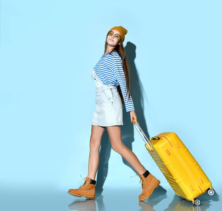 Teen lady in jeans overall skirt, striped sweatshirt, sunglasses, boots and hat. Smiling, walking with yellow suitcase against blue background. Hipster style, fashion, beauty. Copy space. Full length