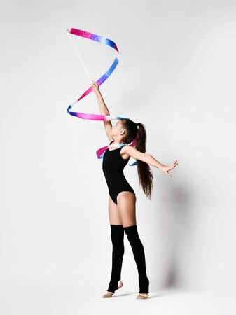 Young girl gymnast in black sport body and uppers standing and making exercise with gymnastic tape over white background. Rhytmhic gimnastics beauty cocnept