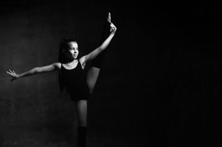 Young smiling girl gymnast in black sport body and special footwear standing, holding stretched leg in hand and keeping balance over dark background. Rhytmhic gimnastics beauty cocnept Stock fotó