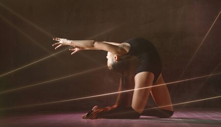 Little girl gymnast star in black sport body and special footwear doing gymnastic pose over dark background with rays of spotlights. Rhythmic Gymnastics Beauty Concept Stock Photo