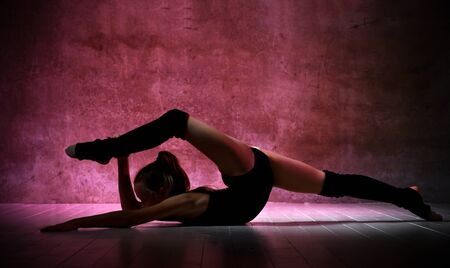 Young girl gymnast in black sport body and uppers lying on floor and holding streched in twine leg over red backlit wall background. Rhytmhic gimnastics beauty cocnept