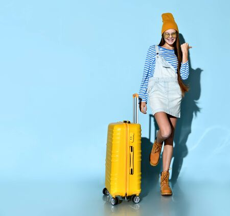 Teenage female in jeans overall skirt, striped sweatshirt, sunglasses, boots and hat. She smiling, posing with yellow suitcase, blue background. Hipster style, fashion, beauty. Copy space. Full length