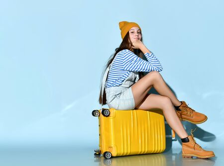 Teenage girl in jeans overall skirt, striped sweatshirt, boots and hat. She smiling, sitting cross-legged on yellow suitcase, blue background. Hipster style, fashion, beauty. Copy space. Full length 写真素材