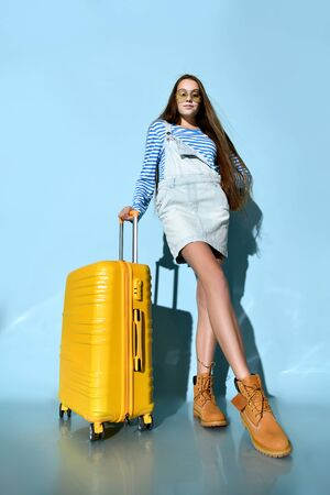 Teen lady in jeans overall skirt, striped sweatshirt, sunglasses and boots. She smiling, posing with yellow suitcase, blue background. Hipster style, fashion, beauty. Copy space. Full length