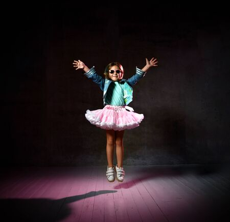 Little girl in t-shirt, denim jacket, poofy skirt, sneakers, sunglasses. She spreading her arms, smiling, bouncing up on black background, pink backlight. Childhood, fashion, advertising. Full length Foto de archivo