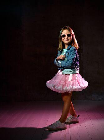 Little schoolgirl in blue t-shirt, denim jacket, poofy skirt, sneakers and sunglasses. Smiling, hands folded, posing on black background, pink backlight. Childhood, fashion, advertising. Full length