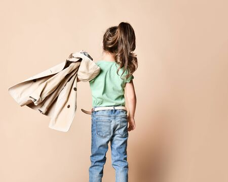 Back View from a little girl with a long curly tail and a beige cloak on one shoulder. Baby fashion concept Banco de Imagens