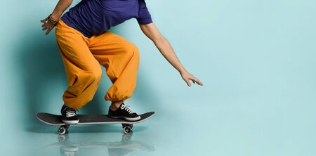 Bearded elderly man in t-shirt, orange pants and hat, gumshoes, bracelets. He crouched while riding black skateboard, posing sideways on blue background. Fashion, style, sport. Full length, copy space