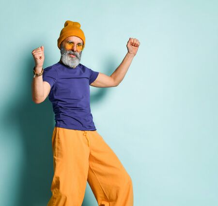 Bearded aged man in purple t-shirt, sunglasses, orange pants and hat, bracelets. He is smiling, pointing at something by forefinger, posing on blue background. Fashion, style. Close up, copy space