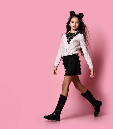 Young slim beautiful brunette girl model in stylish skirt, blouse, boots and accessories walking along pink background in photo studio. Trendy youth casual fashion and beauty concept