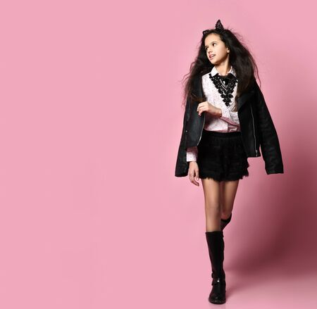 Teenager in white blouse, black leather jacket, boots, skirt, necklace, headband in form of cat ears. She posing on pink studio background. Hipster style, fashion, beauty. Copy space. Full length Stock fotó