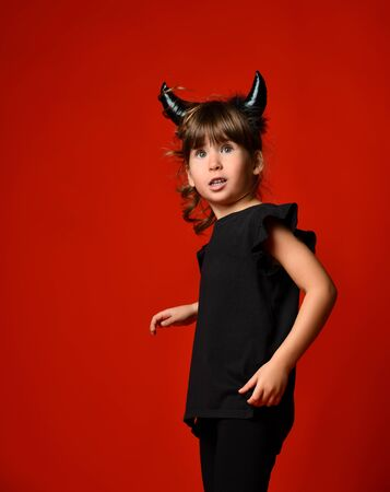 Charming brunette with accessory devilish horns, ponytail, dressed in a black blouse and leggings. She was surprised at something, looking to the side. Masquerade, Halloween. Close
