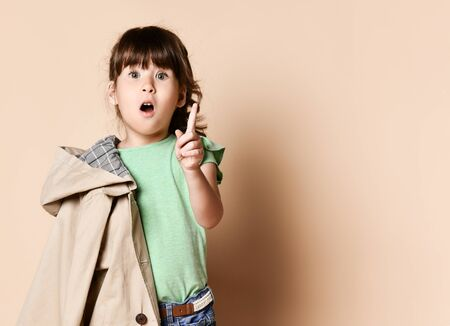 emotional brunette baby girl with a beige raincoat on her shoulder. Shows the index finger up, on a beige background, to the waist