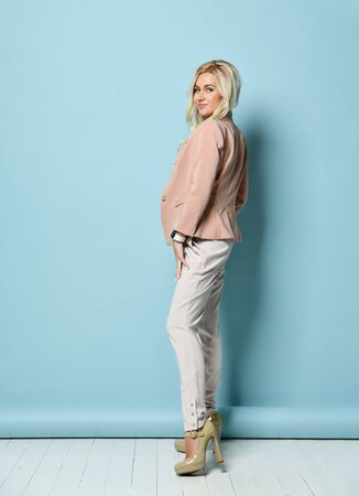Blonde model with long hair, in beige jacket, white overall, high heels. There is watch on her hand. Smiling, posing standing against blue studio background. Beauty, fashion. Copy space. Full length