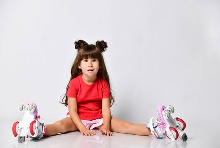 Beautiful girl posing sitting on the floor, in a red t-shirt and shorts and a fashionable hairstyle, in the Studio, with roller skates on her feet