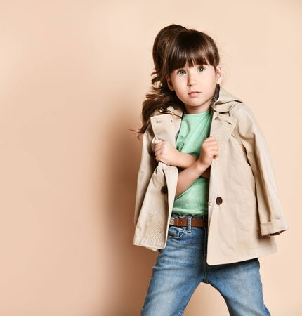 a little brunette girl is holding a raincoat with her arms crossed over her chest. In a green blouse and blue jeans. On a beige background in the Studio Stock Photo