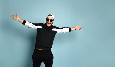 Attractive hipster person in cap, black tracksuit, bracelet and sunglasses. He spread his arms wide and laughing while posing against blue studio background. Trendy outfit. Close up, copy space