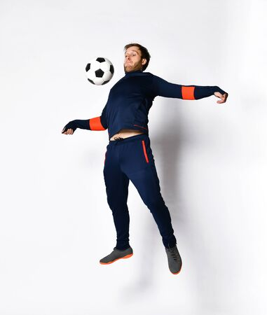 Young man soccer player in blue sportswear and colored sneakers. He is jumping up, performing tricks with ball, posing isolated on white. Concept of sport, balance and agility. Full-length, copy space