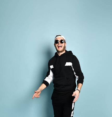 Attractive hipster guy in a cap, black tracksuit, bracelet and sunglasses. He laughs and dances hip-hop on a blue studio background. Fashionable outfit. Close copy space