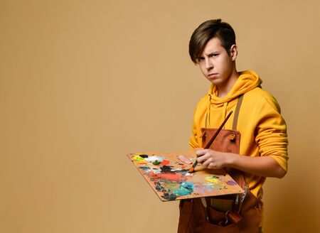 Young painter in yellow hoodie and jumpsuit standing and holding easel, paint and brush in hands over yellow background. Stylish casual clothing for teenagers and creative hobby concept Zdjęcie Seryjne