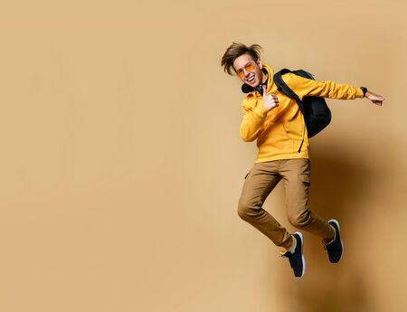 Young teen boy in comfortable clothing, sneakers, sunglasses and backpack jumping and feeling cool over yellow wall background. Stylish casual clothing for teenagers and freedom concept