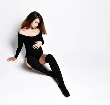Pregnant woman in black leotard and stockings. She is looking at her tummy and smiling, sitting on the floor isolated on white. Family and maternity, sport. Copy space 免版税图像