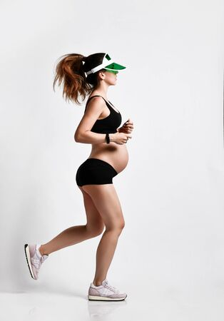 Pregnant girl with belly, in green sun visor, black sport shorts and top, pink sneakers. She is jogging isolated on white background. Family and maternity concepts. Full-length, copy space, side view
