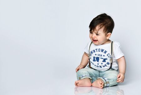 boy in a T-shirt with inscriptions, jeans with suspenders and booties. He is sitting on the floor and crying, isolated on a white background. The concept of articles about childhood or advertising for children. close