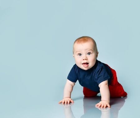 Little chubby child in t-shirt and red shorts. He is creeping on the floor against blue background. Concept for articles about childhood, advertising for babies. Close up, copy space Foto de archivo