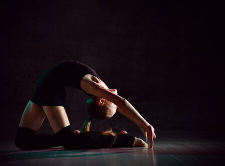 Young girl gymnast in black sport body and special footwear making gymnastic pose over dark background . Rhytmhic gimnastics beauty cocnept