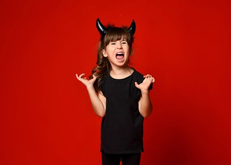 Little brunette kid with devil horns is screaming with closed eyes while posing against a red studio background. Masquerade, Halloween party. Close up